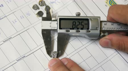 pólos : closeup technician measures small parts with digital meter