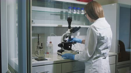 petroleum refinery : motion past girl lab assistant looking at microscope during test Stock Footage