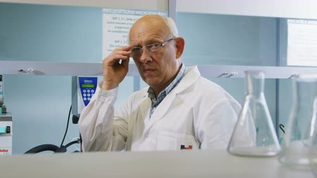 surový : lab employee puts on glasses and takes bulb for oil test