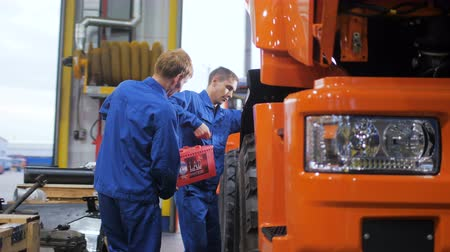 nikl : technicians install powerful accumulator on lorry in workshop