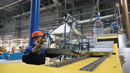 nikl : camera moves to conveyor belt and crane puts metal workpieces