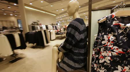 разница : camera moves around fashion store racks with new clothes Стоковые видеозаписи