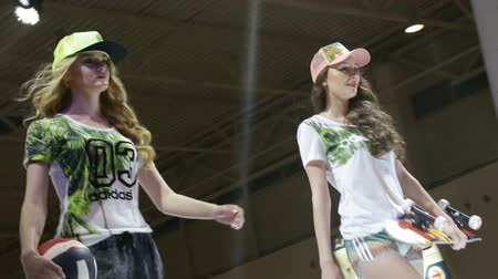 строк : long haired ladies walk in modern sporty clothes on podium