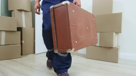 materiaŁ : loader carries old large brown case into room with boxes