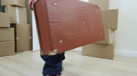 replace : man carries old soviet valise into room filled with boxes