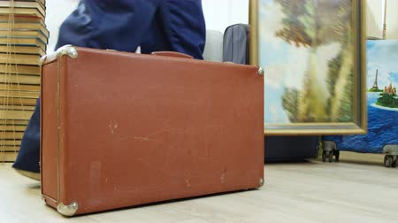 relocate : man puts picture at new suitcase near books by soviet valise Stock Footage