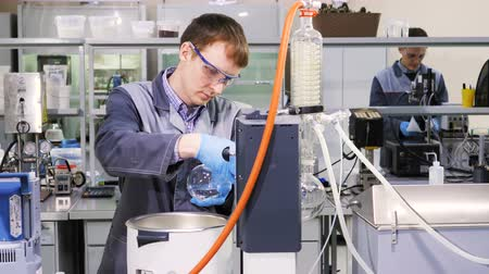 clear the table : scientist in grey coat connects lab glass to device Stock Footage