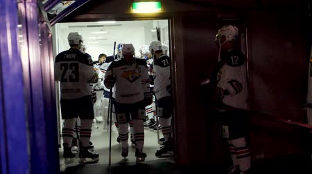 ice hockey rink : slow motion hockey players go out of changing room at game Stock Footage