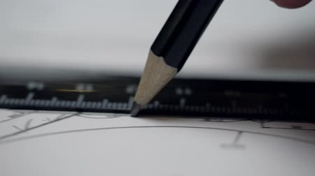 close view pencil moves along black ruler to drawer fingers Stock Footage