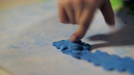 closeup child hand makes sky on picture with blue plasticine