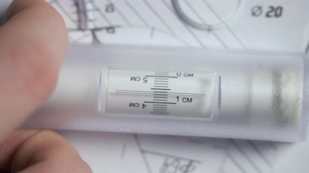 macro hand moves rolling ruler along detail drawing