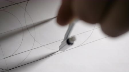 closeup constructor draws circle with compass on white paper