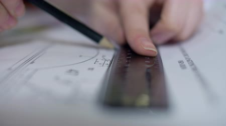 macro female engineer draws detail with pencil and ruler Stock Footage