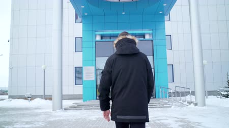 носить : backside view man in jacket walks to office center entrance Стоковые видеозаписи