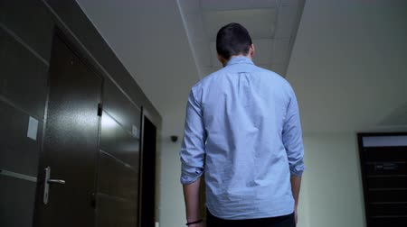 backside view young man walks along hallway in center