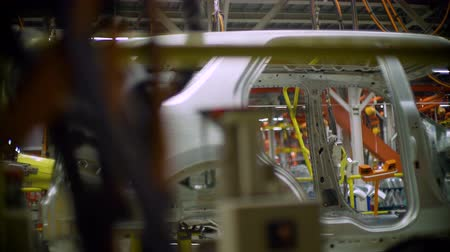 motion by car assembly line with automobile carcass at plant Stock Footage