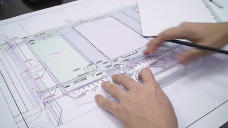 closeup engineer works with equipment drawing at table