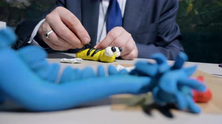 пластилин : closeup man makes plasticine stripes for toy bee at table