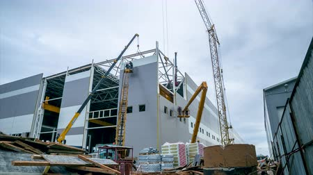 enviroment : timelapse construction of storehouse with cranes against sky