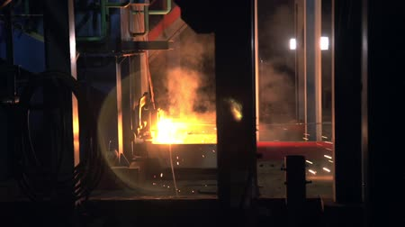 metallurgical : molten metal pours into container with flame sparkles