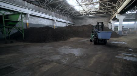 stockpile : forklift loader drives along storehouse full of metal ore