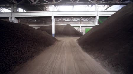 entre : motion between raw metal ore heaps in spacious storehouse