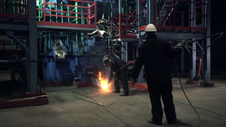 metallurgical : workers control process of metal melting at small furnace