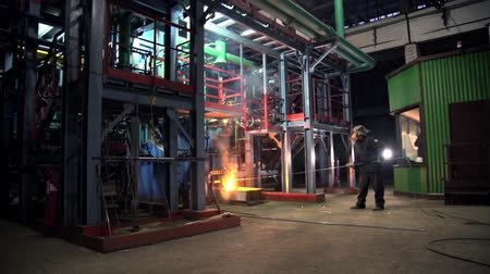 metallurgical : skilled employee in mask works on metal melting furnace Stock Footage