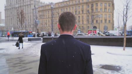 vagabundo : businessman in office suit walks along city square in winter