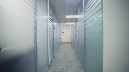 проходить : motion along hallway between offices with glass walls