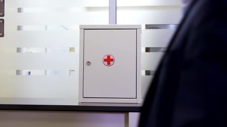 first aid kit : first aid kit box with red cross on shelf in modern office