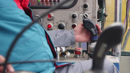 lever : worker controls machines with levers at plant closeup