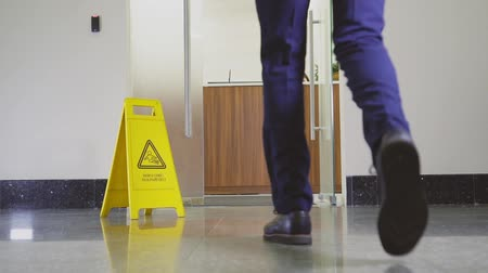 csikk : businessman comes into office past sign wet floor backside
