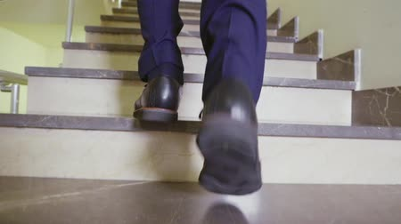 oficial : man goes up stairs slow motion low angle shot closeup