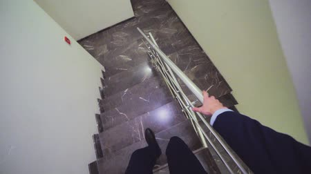 corrimão : businessman walks down marble stairs view from headcam