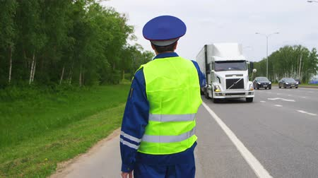 truck stop : traffic inspector shows stop sign to white lorry on highway