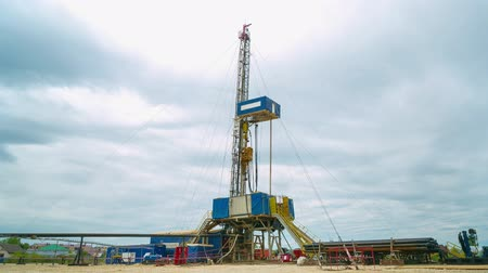 field survey : geodetic station with drill operates at oil field timelapse Stock Footage