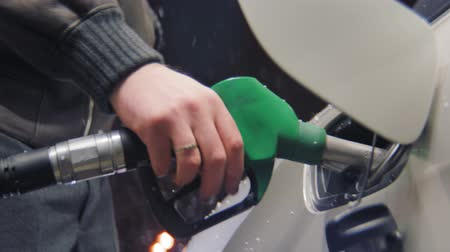 filling station : man refuels auto on gasoline station at snowfall closeup