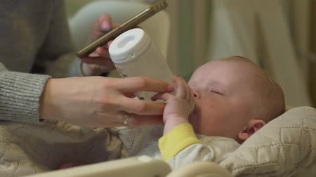 bottle feeding : Mother Feeding Baby milk and using mobile phone together