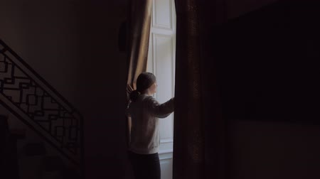 Girl Opens Curtains In Dark Stock Footage