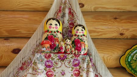 aninhada : Group of nested dolls on a shelf in the background towels and wooden wall