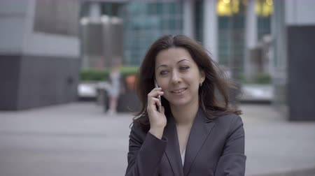 sucessful : Attractive woman in business clothes approaching to the camera while talking on a mobile phone on the background buildings business centers, UHD 4K