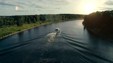 Aerial view of a private white motor boat floats slowly on the river to the sunset direction and the blue waves diverge at both bakes. The motor of a boat is very quiet and doesnt break the silence.