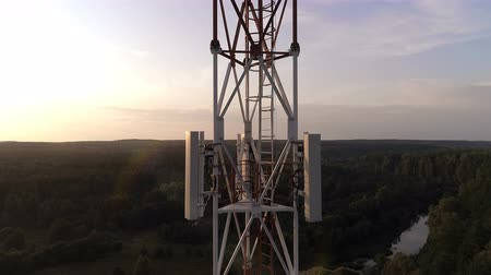 alıcı : Closeup aerial view of the telecommunications tower. There at the top of a telecom tower installed antennas that transmit signal of cellular 5g 4g networks and mobile operators over long distances.
