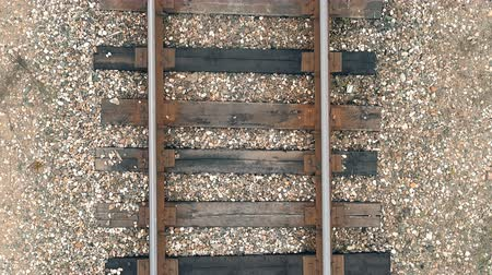 macadam : Aerial view to old federal railroad and rails with wooden sleepers close up. The high detail video shows steel rails with bolts and rivets, wooden sleepers with cracks and gravel stones. Stock Footage