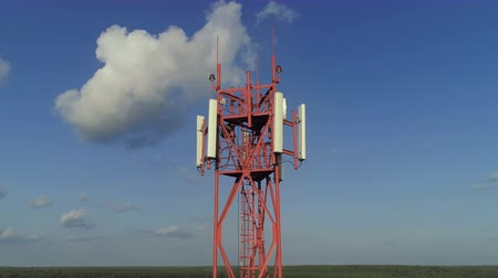 gsm : Aerial view around of the telecommunication tower against blue sky. On the top of a telecom tower installed antennas and transmitter which transmits the signals of cellular 5g 4g mobile signals. Stock Footage