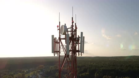 jel : Closeup aerial shot around of telecommunication tower in a rural location. Telecom tower antennas and satellite transmits the signals of cellular 5g 4g mobile signals to the consumers and smartphones.