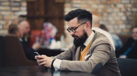 Modern hipster businessman in glasses using mobile phone