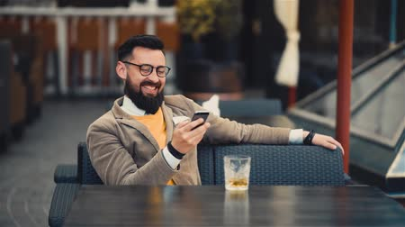 Happy bearded man looking at mobile phones screen and smiling Wideo