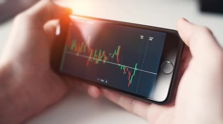 a man checking stock market on smartphone Wideo